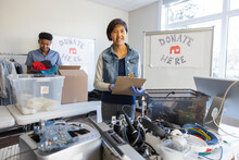 Portrait Confident Teenage Girl Volunteer Sorting Electronic Donations