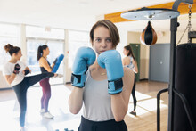 Portrait Confident Tough Teen Girl In Boxing Gloves In Gym Studio