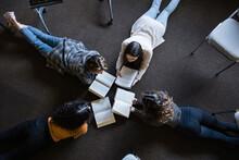 Teen Girl Friends Reading In Book Club Meeting In Circle On Floor