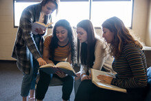 Teen Girl Friends Reading In Book Club Meeting