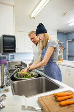 Father And Daughter Volunteers Washing Vegetables In Soup Kitchen