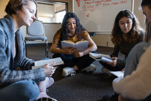 Teen Girl Friends Reading In Circle On Floor At Book Club Meeting