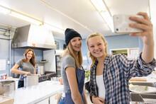 Happy Teen Sisters Taking Selfie Volunteering In Soup Kitchen