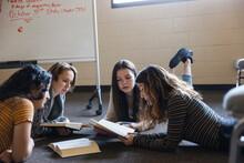 Teen Girl Friends Reading On Floor At Book Club Meeting