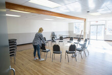 Girl Volunteer Arranging Chairs In Circle In Community Center
