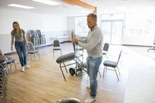 Father And Daughter Volunteers Arranging Chairs In Community Center