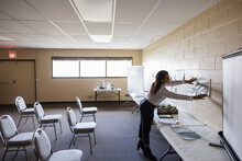 Woman Hanging Urban Planning Maps For Meeting In Community Center