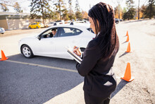 Driving Instructor Grading Student Parking Car In Sunny Parking Lot