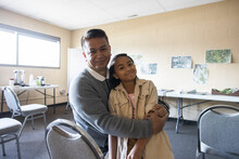 Portrait Happy Father And Daughter Hugging In Community Center