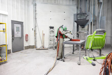 Technician In Protective Clothing Spray Painting Component