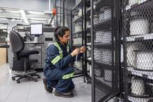 Technician Selecting Wire In Storeroom