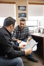Two Men Discussing Report In Office