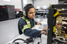 Technician Working On Helicopter Electronics In Workshop