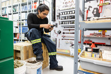 Technician Looking At Phone In Storeroom
