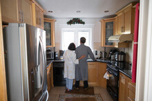Senior Couple In Bathrobe Looking Out Kitchen Window