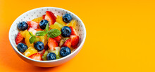 Web Banner With Fresh Summer Salad Of Various Fruits And Berries. Kiwi, Orange, Strawberry And Blueberry On A Plate Decorated With Mint On An Orange Background