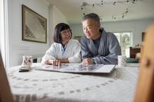 Senior Couple In Bathrobe Browsing Photo Album At Dining Table