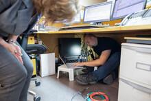 Technician Fixing Wiring Under Desk In Office