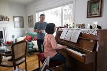 Senior Man Looking At Wife Play Piano At Home