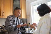Senior Couple In Bathrobe Checking Vitamin Bottle In Kitchen