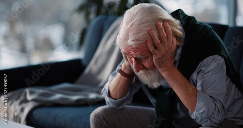 Foto Old unwell caucasian man crying over retirement letter frustrating when learning bad news