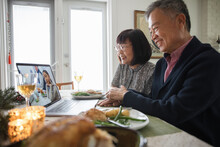 Senior Couple Holding Hands On Video Call With Granddaughter