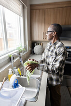 Senior Man Drying Hands At Kitchen Sink, Looking Out Window