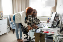 Senior Woman Kissing Husband Using Computer In Home Office