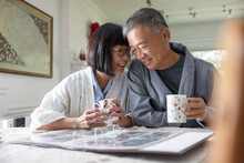 Senior Couple In Bathrobe Browsing Photo Album At Dining Table