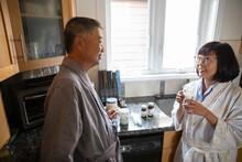 Senior Couple In Bathrobe Talking In Kitchen
