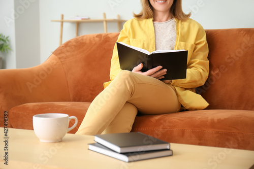 Obraz Woman reading book at home - fototapety do salonu