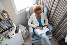 Senior Woman Reading Book In Armchair