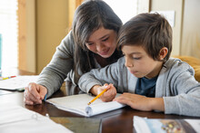 Woman With Down Syndrome Helping Nephew With Homework At Table