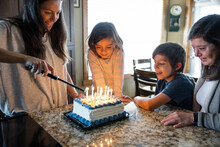 Mother Lighting Up Candles On Birthday Cake At Home
