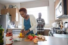 Senior Woman Cutting Vegetable On Worktop