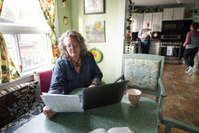 Senior Woman Working With Laptop At Dining Table