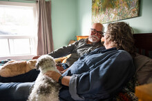 Senior Couple Relaxing On Bed With Pets