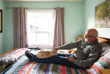 Senior Man Relaxing On Bed With Cat