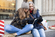 Mother And Teen Daughter With List Taking Break Christmas Shopping