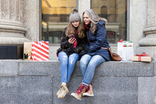 Mother And Teenage Daughter With Smart Phone Christmas Shopping