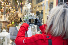Senior Woman With Smart Phone Photographing Winter Shop Window Display