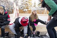 Family Putting On Ice Skates At Backyard Ice Hockey Rink