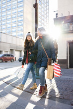 Mother And Daughter With Shopping Bags Arm In Arm On City Street
