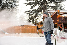Man With Hose Spraying Backyard Ice Hockey Rink With Water