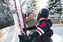 Happy Father And Son At Ice Hockey Net On Sunny Backyard Ice Rank