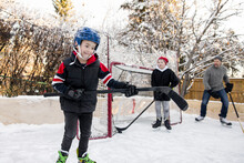 Happy Boy Playing Ice Hockey With Family On Backyard Ice Rink