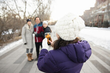 Girl With Smart Phone Photographing Family In Winter Park