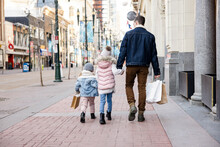 Father And Daughters Holding Hands With Shopping Bags On City Sidewalk