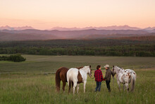 Rear View Of Couple And Horses In Foothills Overlooking Mountains
