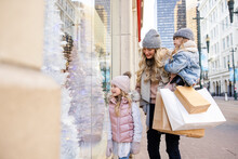Mother And Daughters Looking At Christmas Window Display In City